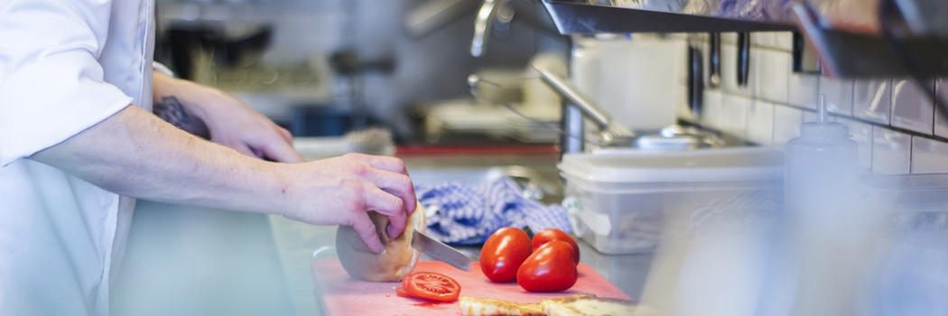 Nutrition Services worker cuts tomatoes in the kitchen.